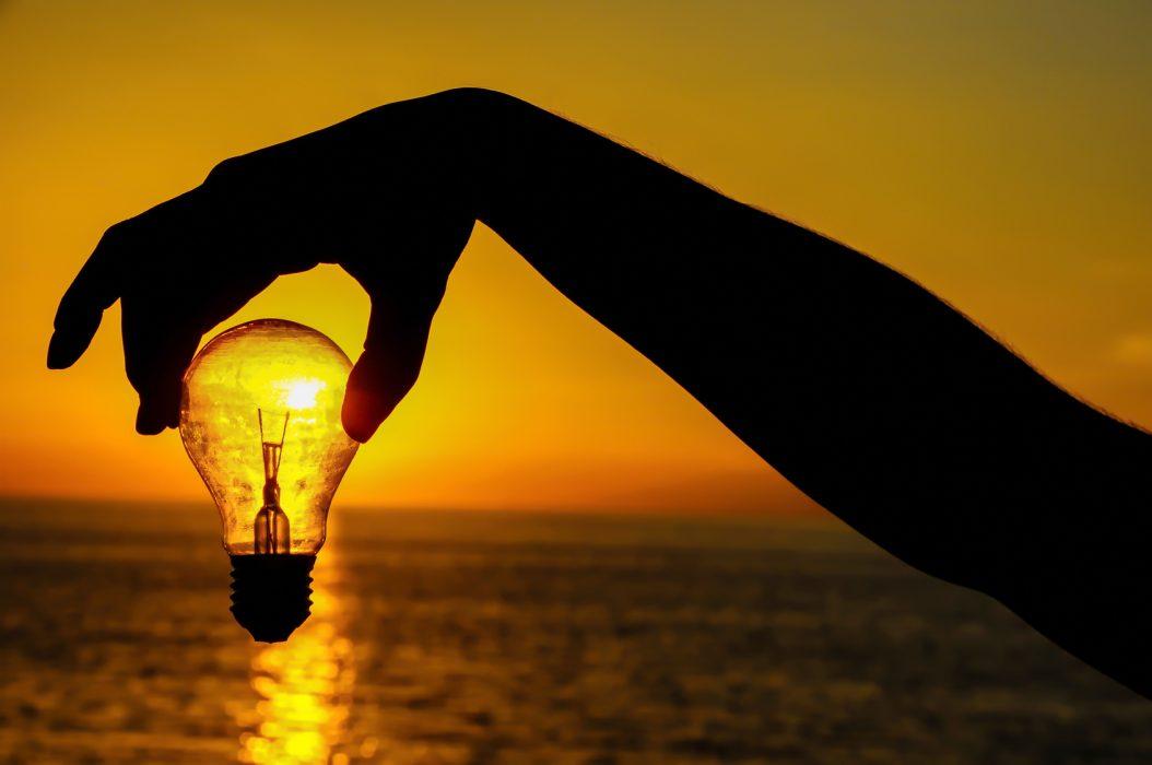 Energy Concept Light Bulb And Sun Setting On The Atlantic Ocean